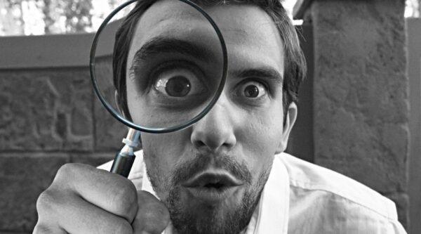 Man looking forward with magnifying glass
