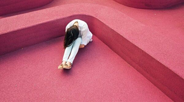 Sad woman, head down, sitting on floor alone