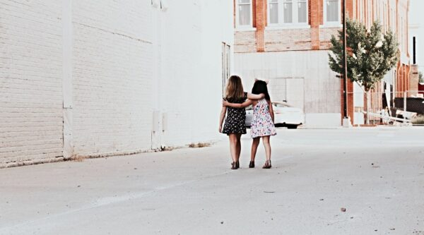 Two girls walking arm in arm