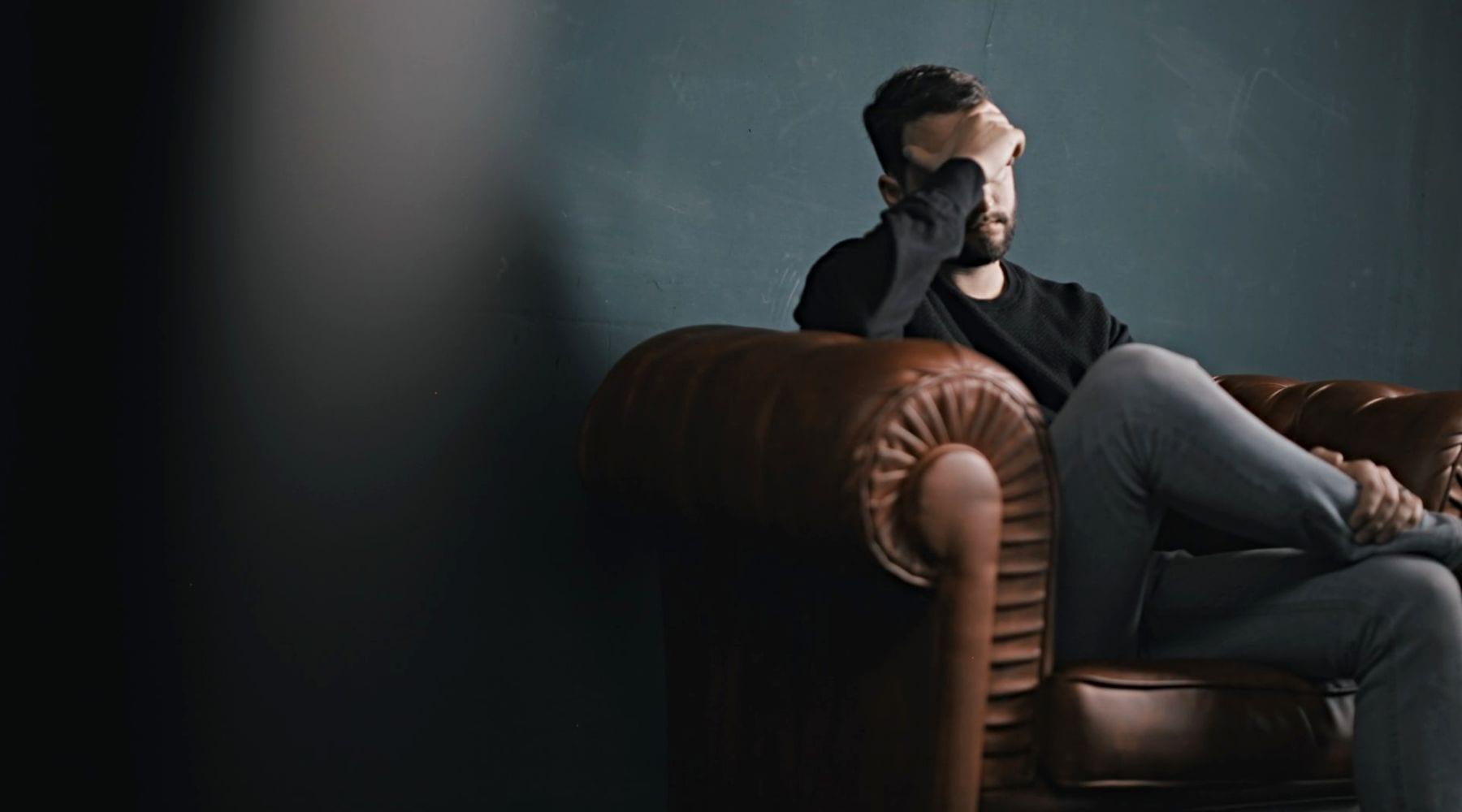 Sad man sitting alone on sofa