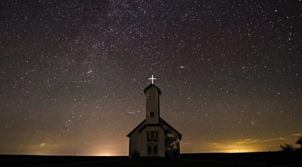 Silhouetted church with lit cross against starry sky