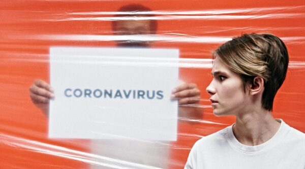 Woman separated from man holding coronavirus sign