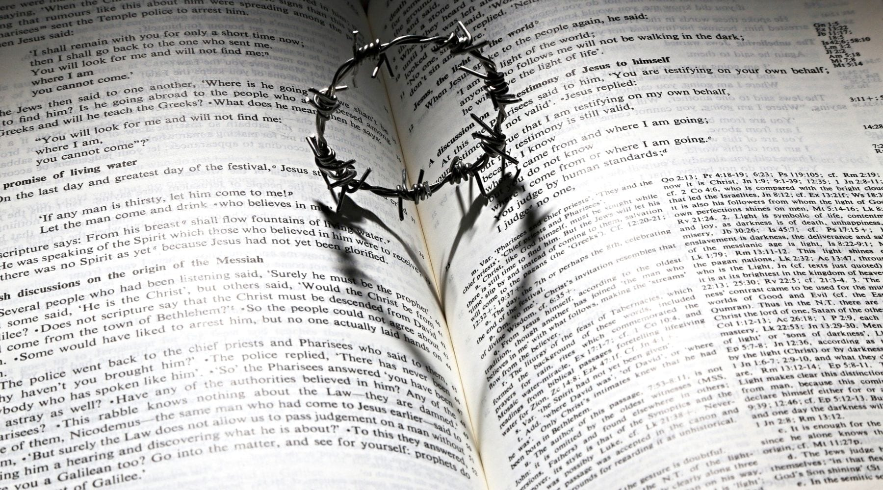 Crown of thorns casting heart shadow on Bible pages