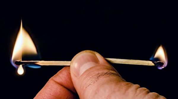 Hand holding two burning matches
