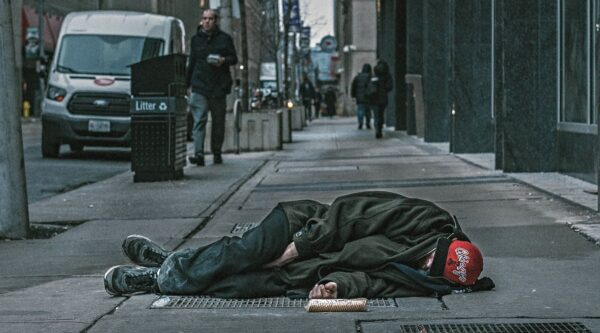 Homeless person sleeping on city sidewalk