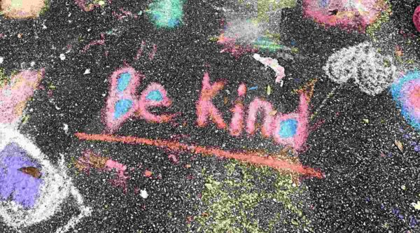 Artwork of 'be-kind' graffiti written in chalk