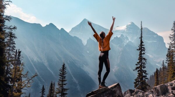 Celebratory woman standing on mountain peak