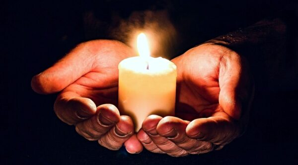 Two hands cradling a lit candle
