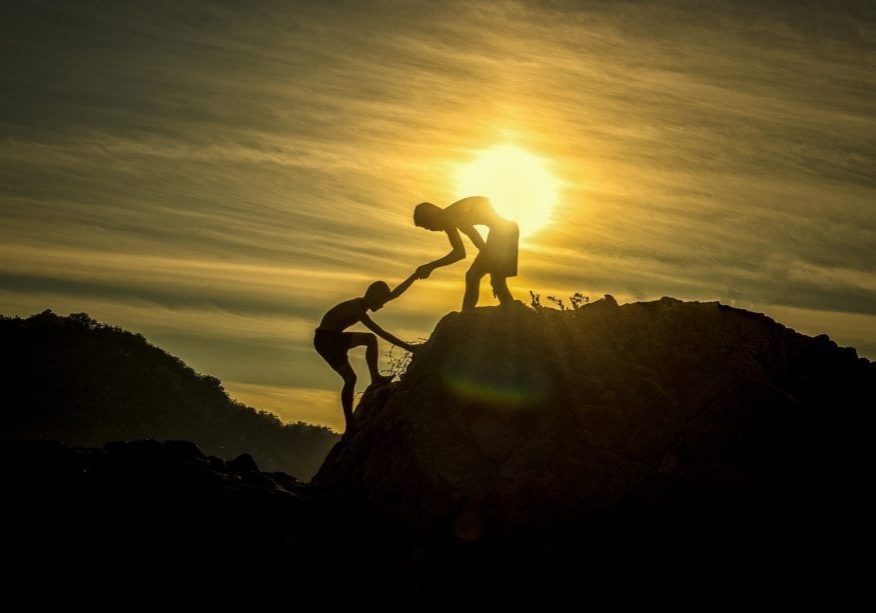 a man helping another man up with a sun behind them