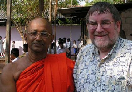 Paul Montacute (right), greeted by a Buddhist priest in Sri Lanka in February. (Photo by Robert Parham)