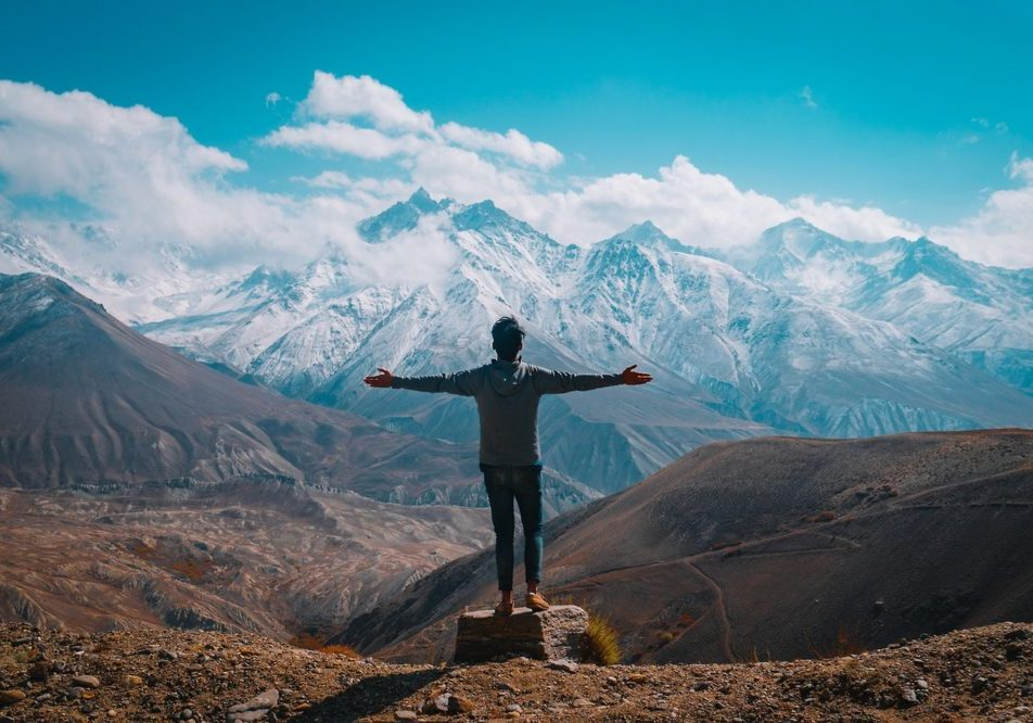 person standing on a mountain with arms outstretched